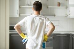 在人手的背面图在他的臀部,观察厨房 图库摄影