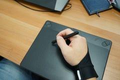 在人手设计师用途有触摸屏的图形输入板上看法  免版税库存照片