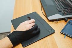 在人手设计师用途有触摸屏的图形输入板上看法  库存照片