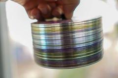 在人的一把手修平刀堆积的CD的圆盘 免版税库存图片