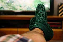 在人的在家变冷脚的看着电视的被编织的snoozies 免版税图库摄影