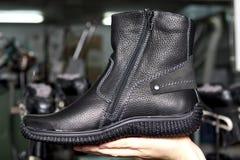 在人的手上的起动 生产设计师鞋子 鞋类produc 免版税库存照片