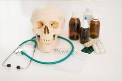 在人的头骨听诊器和药物的特写镜头在桌上 免版税库存照片