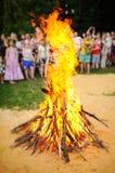 在人背景的大篝火  免版税库存照片