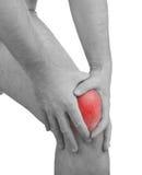 在人膝盖的剧痛。对膝盖ach斑点的男性举行的手  免版税库存图片