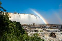 在人行桥的夫妇与在伊瓜苏瀑布的彩虹 免版税图库摄影