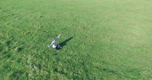 在人附近的低轨道飞行与笔记本垫的绿草的在黄色农村领域 影视素材