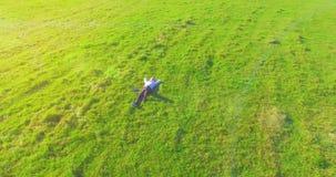 在人附近的低轨道飞行与笔记本垫的绿草的在黄色农村领域 股票视频