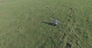 在人附近的低轨道飞行与笔记本垫的绿草的在黄色农村领域 股票录像