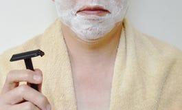 在人面孔的剃须膏与在右手的剃具准备对刮 免版税图库摄影