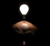 在人头之上的浮动的被点燃的电灯泡 库存图片