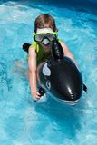 在今后游泳的水池的年轻男孩骑马浮游物 免版税库存照片