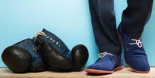在仍然是在工作服的一个人旁边的拳击手套 免版税库存图片