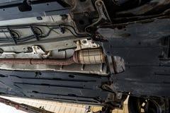 在从下面被看见的汽车的排气系统,汽车在推力在汽车车间 免版税图库摄影