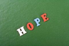 在从五颜六色的abc字母表块木信件组成的绿色背景,广告文本的拷贝空间的希望词 了解 免版税库存图片