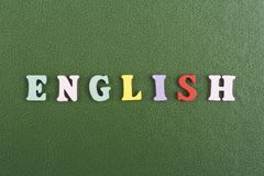在从五颜六色的abc字母表块木信件组成的绿色背景,广告文本的拷贝空间的英国词 库存照片