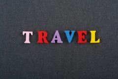 在从五颜六色的abc字母表块木信件组成的黑委员会背景,广告文本的拷贝空间的旅行词 库存图片