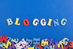 在从五颜六色的abc字母表组成的蓝色背景的BLOGGING词阻拦木信件,广告文本的拷贝空间 免版税图库摄影
