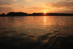 在从在水的一条小船观看的岸天际上的日落 免版税库存图片