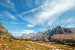 在从暗藏的湖供徒步旅行的小道看的摇石通行证的双突透镜的云彩在冰川国家公园在2017秋天火期间在蒙大拿 免版税库存图片