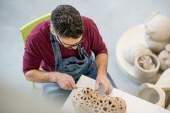 在从未加工的黏土的一个围裙雕刻的雕象穿戴的陶瓷技师Topview在明亮的陶瓷车间 图库摄影
