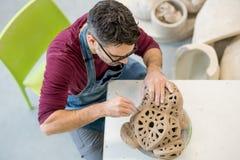 在从未加工的黏土的一个围裙雕刻的雕象穿戴的陶瓷技师Topview在明亮的陶瓷车间 库存图片