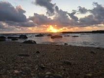 在从海滩看见的太平洋上的日出在考艾岛海岛,夏威夷上的Kapaa 库存照片