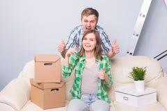 在他们新的家庭举行的钥匙的愉快的夫妇 免版税库存图片