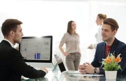 在他们的会议期间,资深和小辈商人谈论某事 免版税库存照片