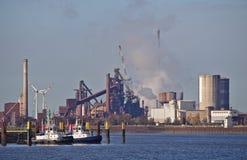 在他们的停泊的两条猛拉小船与散发烟云和风力驻地的巨大的钢铁厂在背景中 库存照片