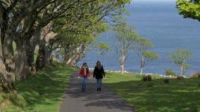 在他们的旅途上的两年轻女人沿堤道海岸在北爱尔兰 股票视频