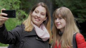 在他们的旅途上的年轻女人到Glencar瀑布在爱尔兰 股票视频