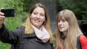 在他们的旅途上的年轻女人到Glencar瀑布在爱尔兰 股票录像