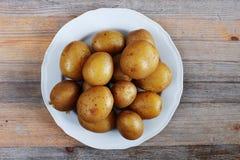 在他们的皮肤的煮的土豆在板材 免版税库存照片