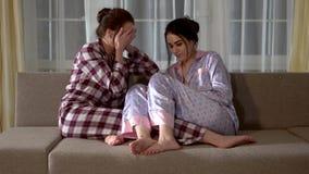 在他们的睡衣的两孪生观看一可怕恐怖电影的坐长沙发 关系姐妹 股票录像