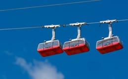 在他们的绳索的三条红色玩具空中览绳 库存照片
