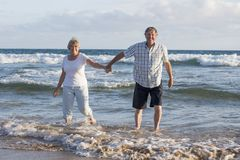 在他们的60s或70s的可爱的资深成熟夫妇退休了走愉快和轻松在海滩在浪漫一起变老的海岸 免版税库存照片