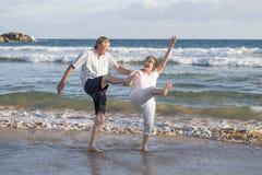 在他们的60s或70s的可爱的资深成熟夫妇退休了走愉快和轻松在海滩在浪漫一起变老的海岸 图库摄影
