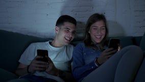 在他们的20s的年轻愉快和浪漫夫妇使用一起享用的手机在家坐笑沙发的长沙发获得乐趣 股票录像