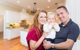 在他们美丽的厨房里面的年轻军事家庭 免版税图库摄影