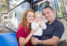 在他们美丽的RV前面的愉快的年轻军事家庭 免版税图库摄影