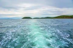 在他后漂浮小船水和泡影一根美丽的羽毛在您能看到海岛的天际 免版税库存照片