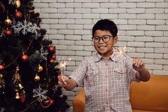 在他的两只手上的亚洲孩子画象拿着闪烁发光物 库存照片