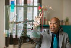 在他的办公室指向在未来派G的圆形统计图表的商人 免版税库存图片