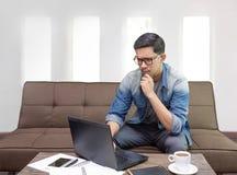 在他的在家看膝上型计算机工作的工作的亚洲人cencentrate作为自由职业者 免版税图库摄影