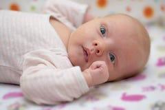 在他的在小儿床一个逗人喜爱的新出生的婴孩的画象 库存照片