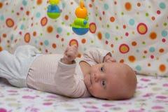 在他的在小儿床和戏剧与垂悬一个逗人喜爱的新出生的婴孩的画象戏弄 免版税图库摄影