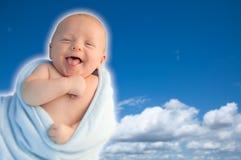 在他的在蓝天的毯子包裹的美丽的笑的男婴 图库摄影