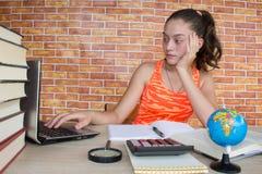 在他的家庭作业的女孩工作 在家学习在书桌上的女孩 免版税库存图片
