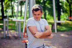 在他的手肘的人感觉在的痛苦在体育期间和锻炼 库存照片